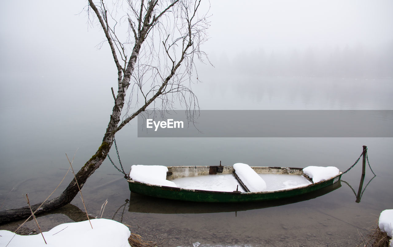 High Angle View Of Frozen Boat Moored In Lake