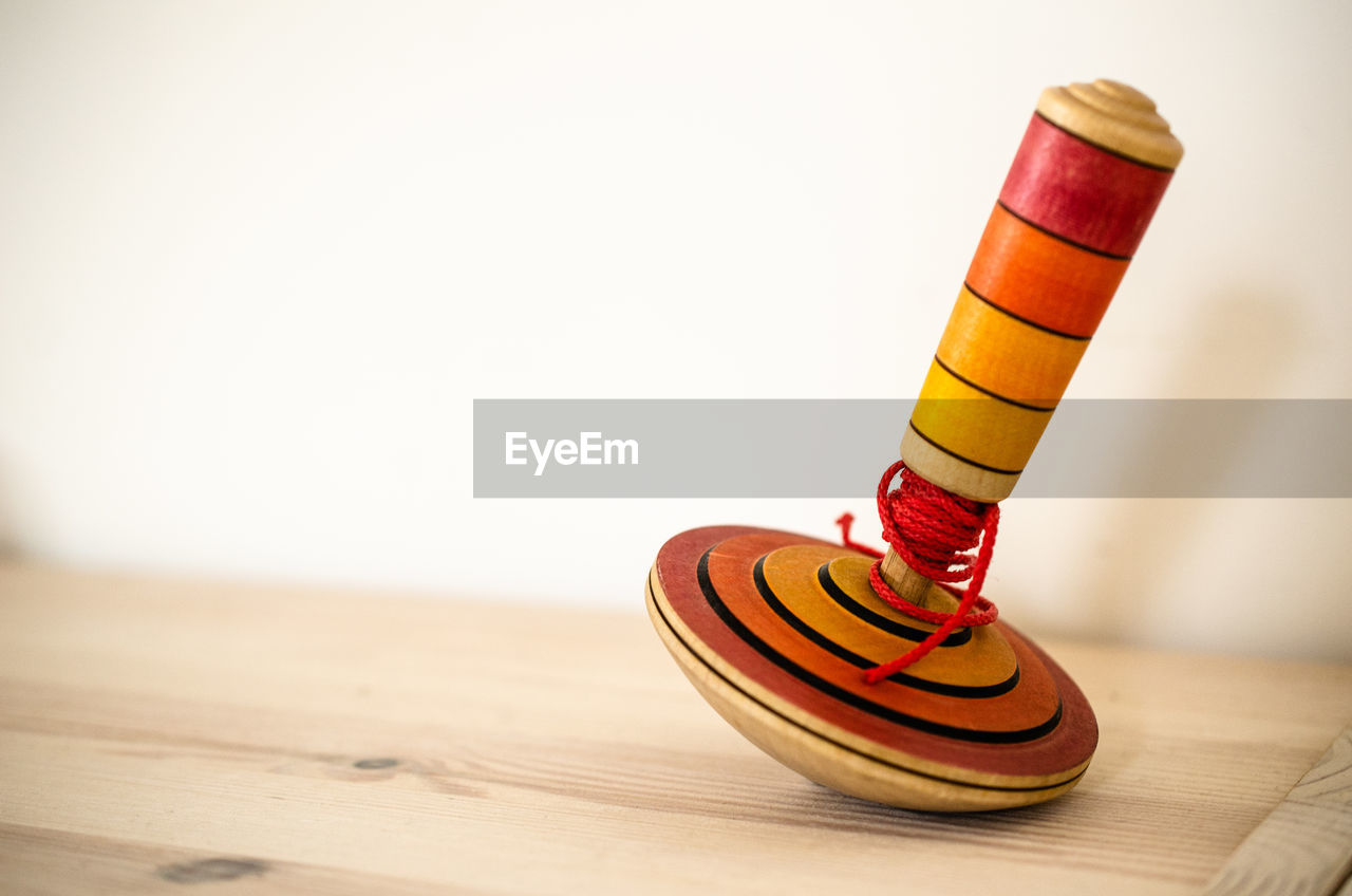 Close-up of spinning top on table against white wall