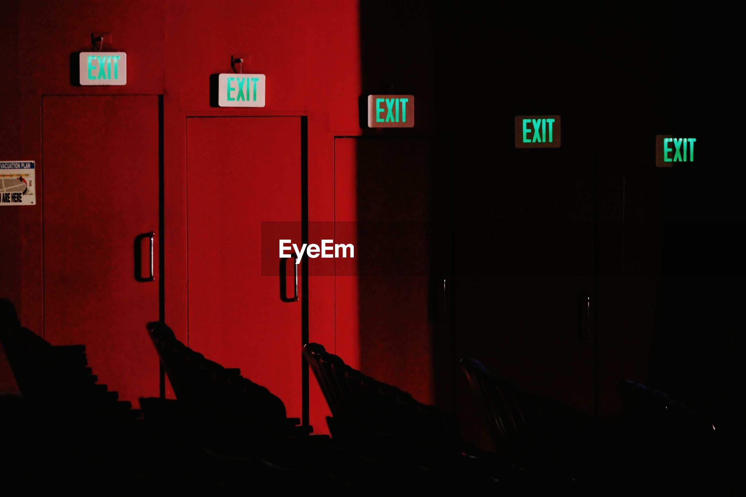 Exit signs on red wall at night