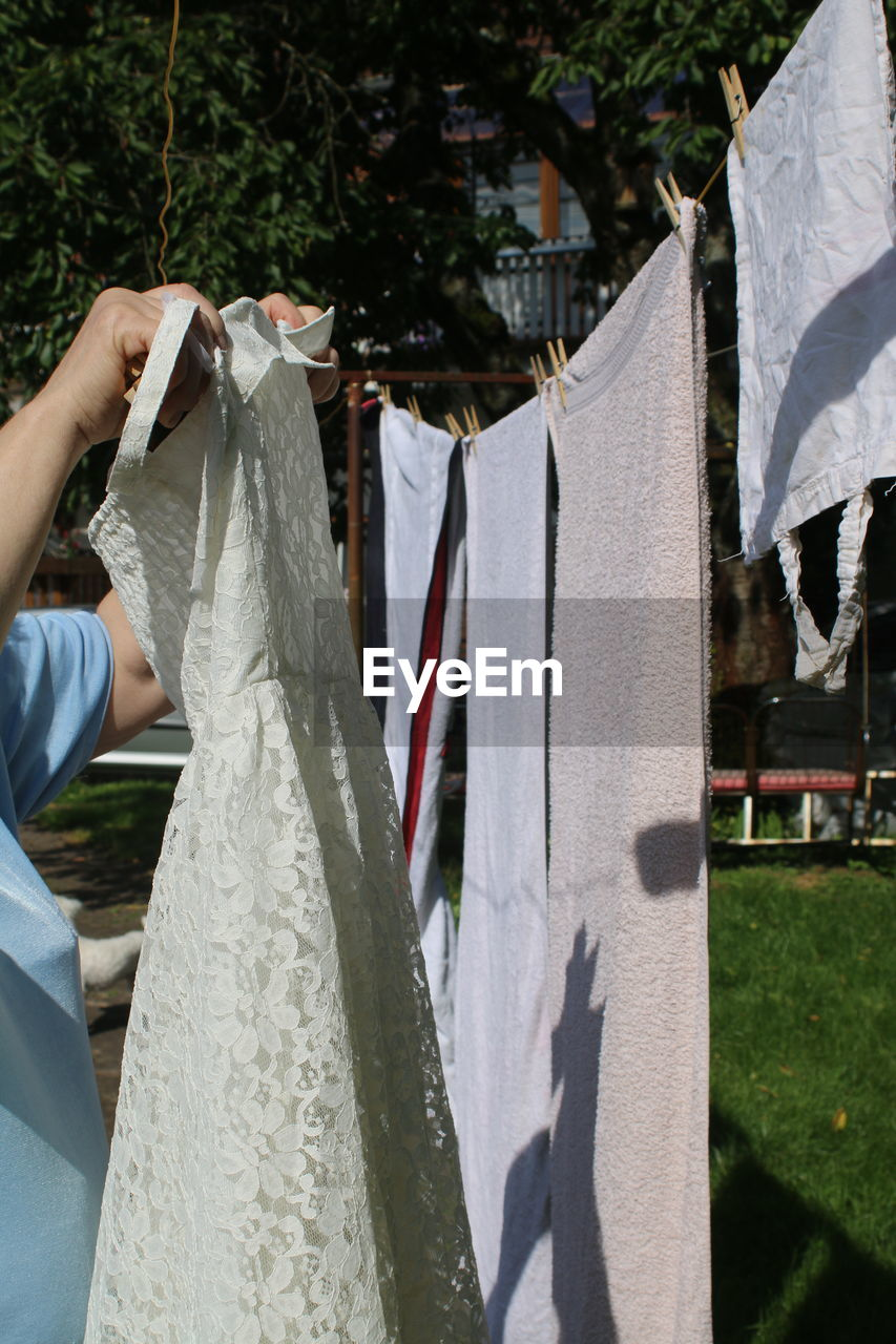 Cropped Image Of Women Holding Dress While Standing By Clothesline In Yard