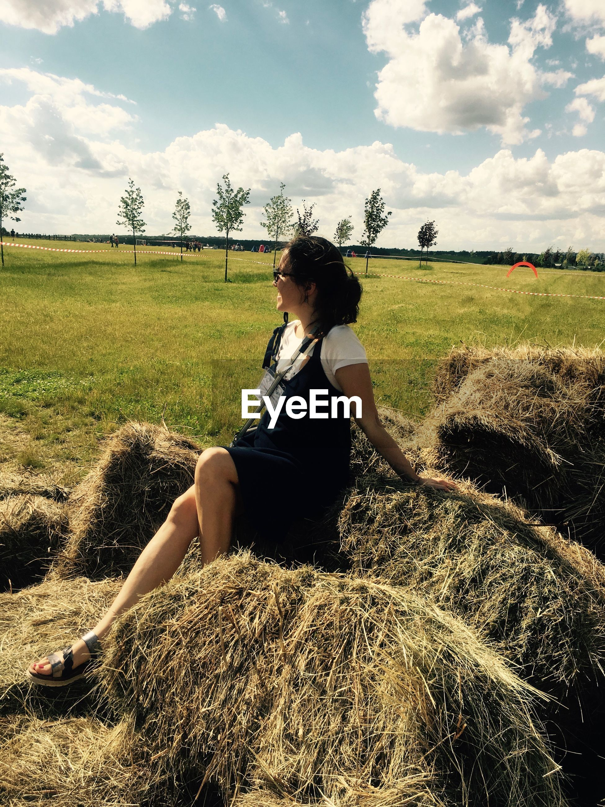 Full length of smiling woman sitting on hay bale against sky during sunny day