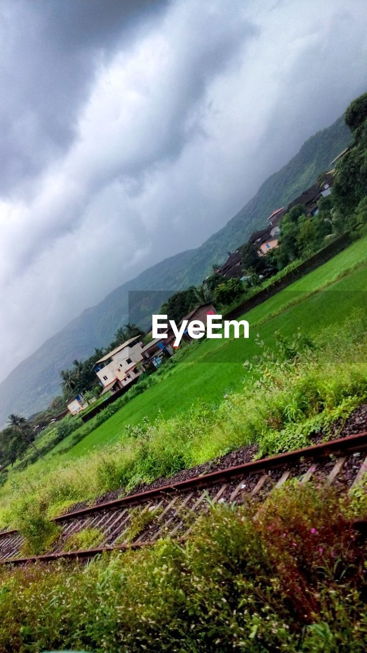 mountain, sky, landscape, day, nature, beauty in nature, grass, scenics, outdoors, cloud - sky, field, water, growth, mountain range, built structure, no people, tree, architecture