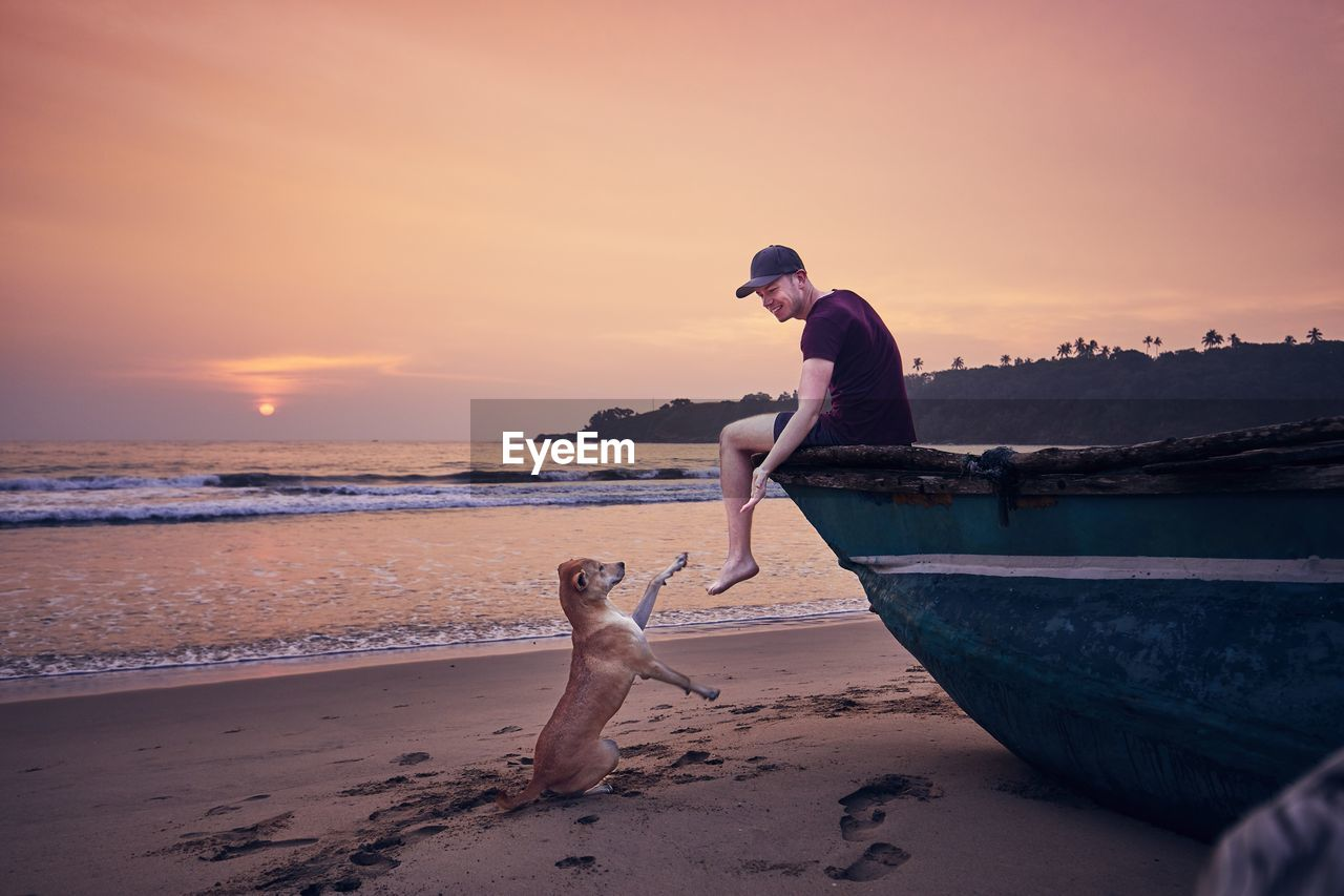 Side view of smiling man playing with dog while sitting at beach against sky during sunset