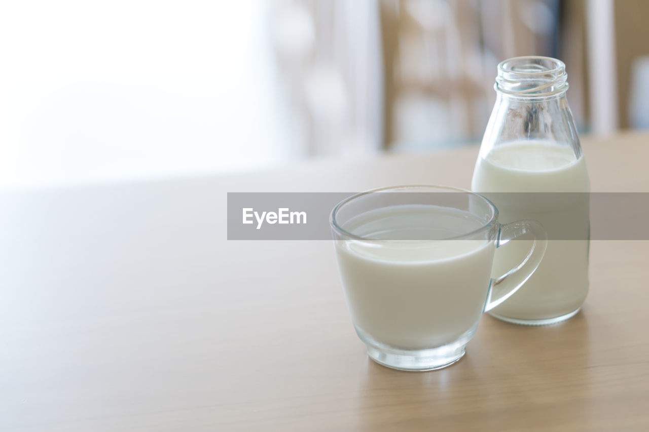 drink, milk, food and drink, table, drinking glass, milk bottle, refreshment, focus on foreground, indoors, no people, freshness, healthy eating, close-up, white background, day