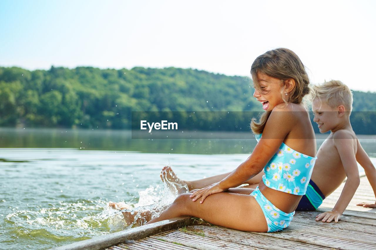 Happy Siblings Splashing Water In Lake Against Clear Sky