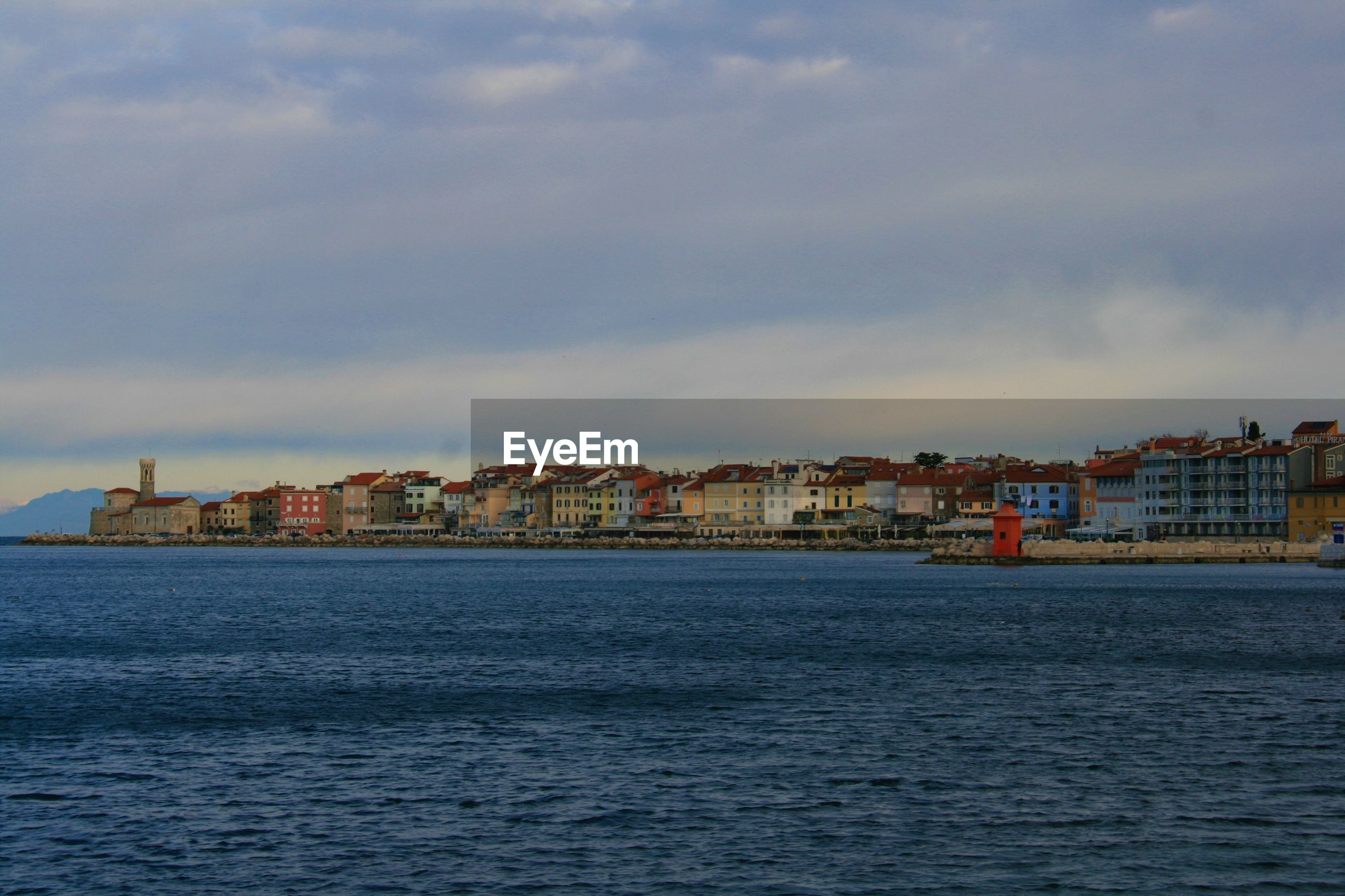 View of townscape by sea against sky
