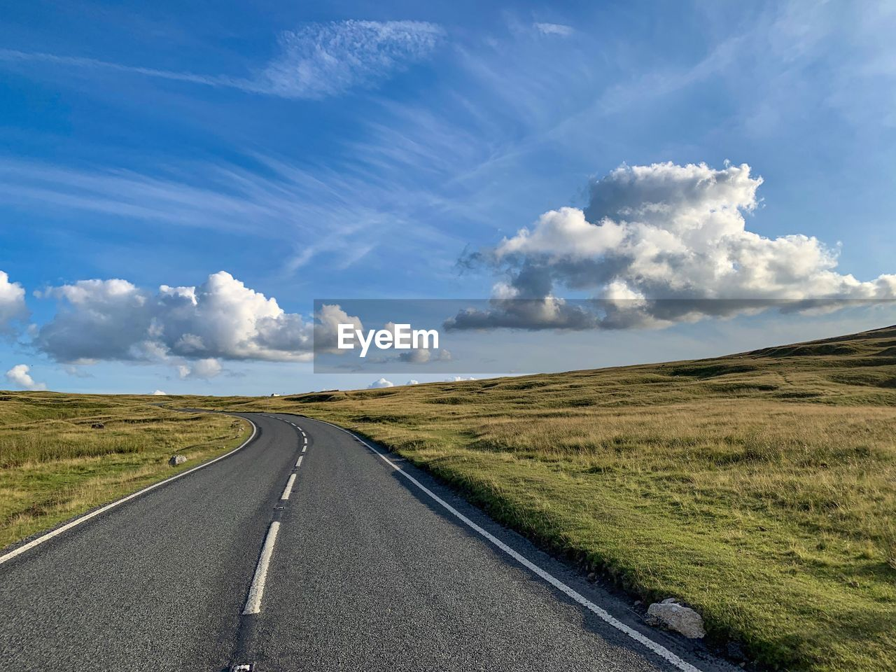 sky, road, cloud - sky, transportation, tranquil scene, nature, the way forward, landscape, land, direction, environment, day, field, beauty in nature, tranquility, scenics - nature, non-urban scene, no people, grass, horizon, diminishing perspective, outdoors, dividing line, long