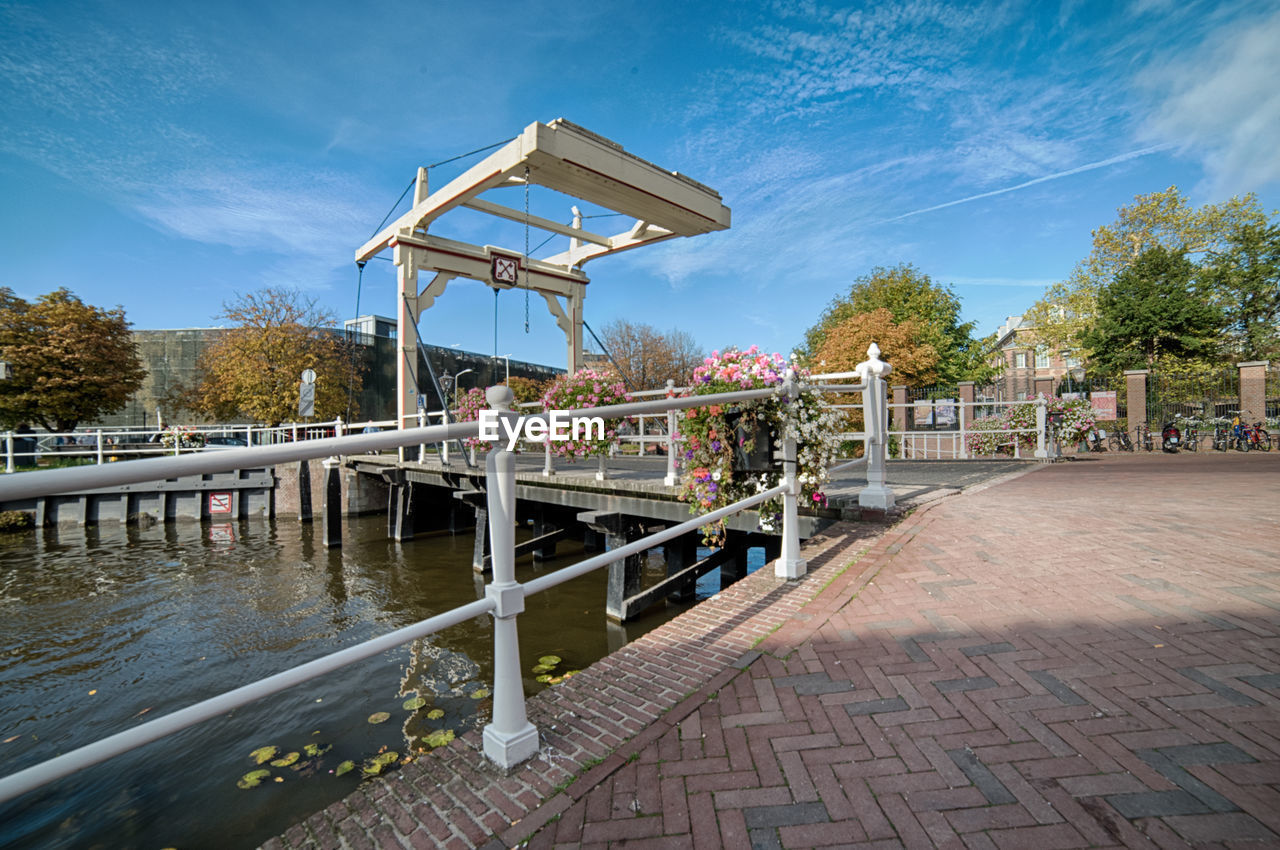 sky, tree, built structure, architecture, nature, plant, railing, water, day, cloud - sky, footpath, outdoors, building exterior, connection, basketball - sport, bridge, blue, men, canal