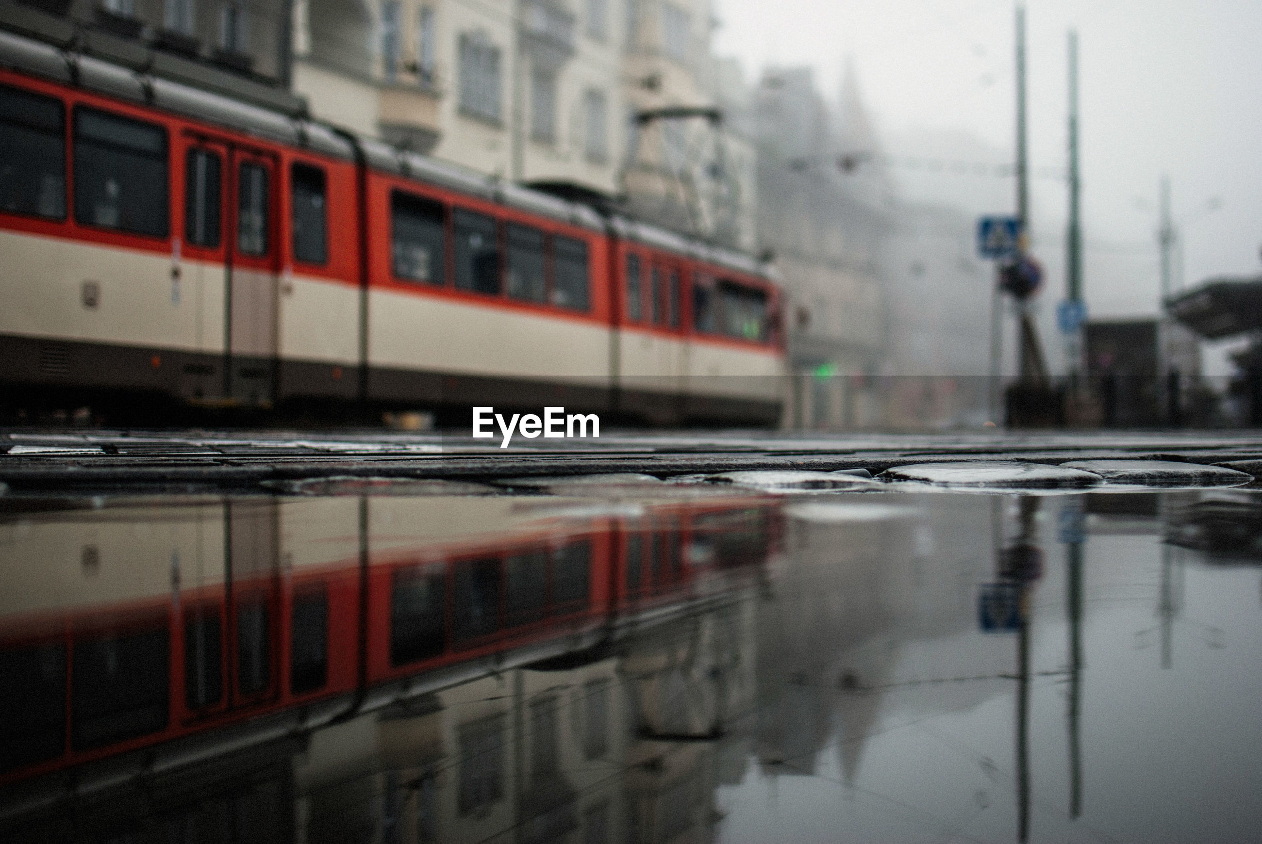 Surface level view of puddle with tram reflection in city