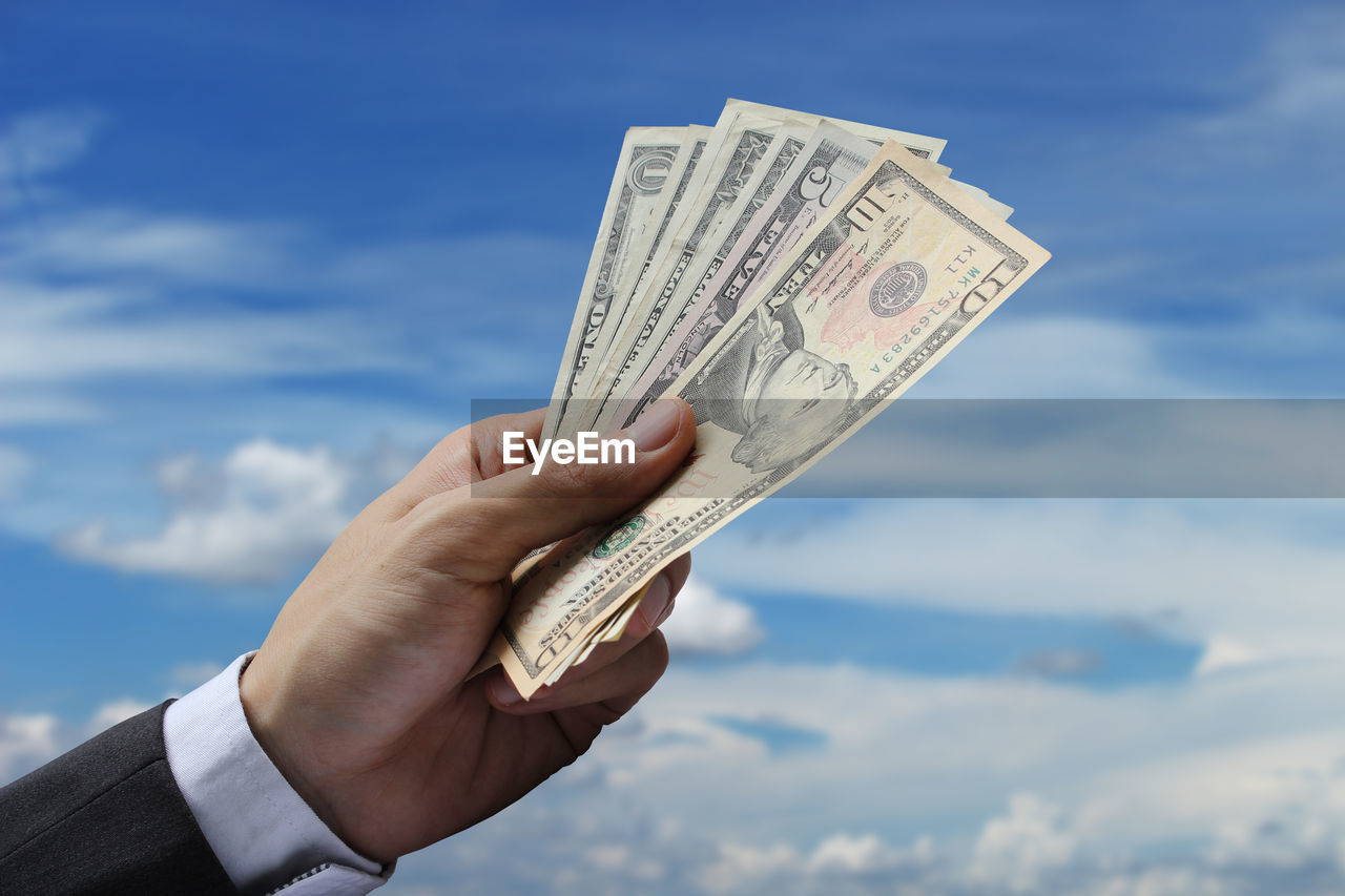 Cropped Hand Of Businessman Holding Paper Currencies Against Cloudy Sky
