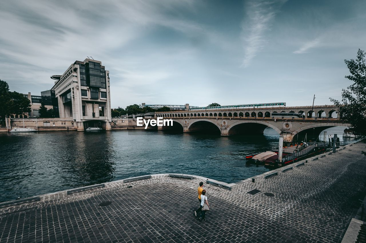 bridge - man made structure, architecture, connection, water, arch, built structure, transportation, sky, river, real people, day, cloud - sky, building exterior, outdoors, one person, full length, people