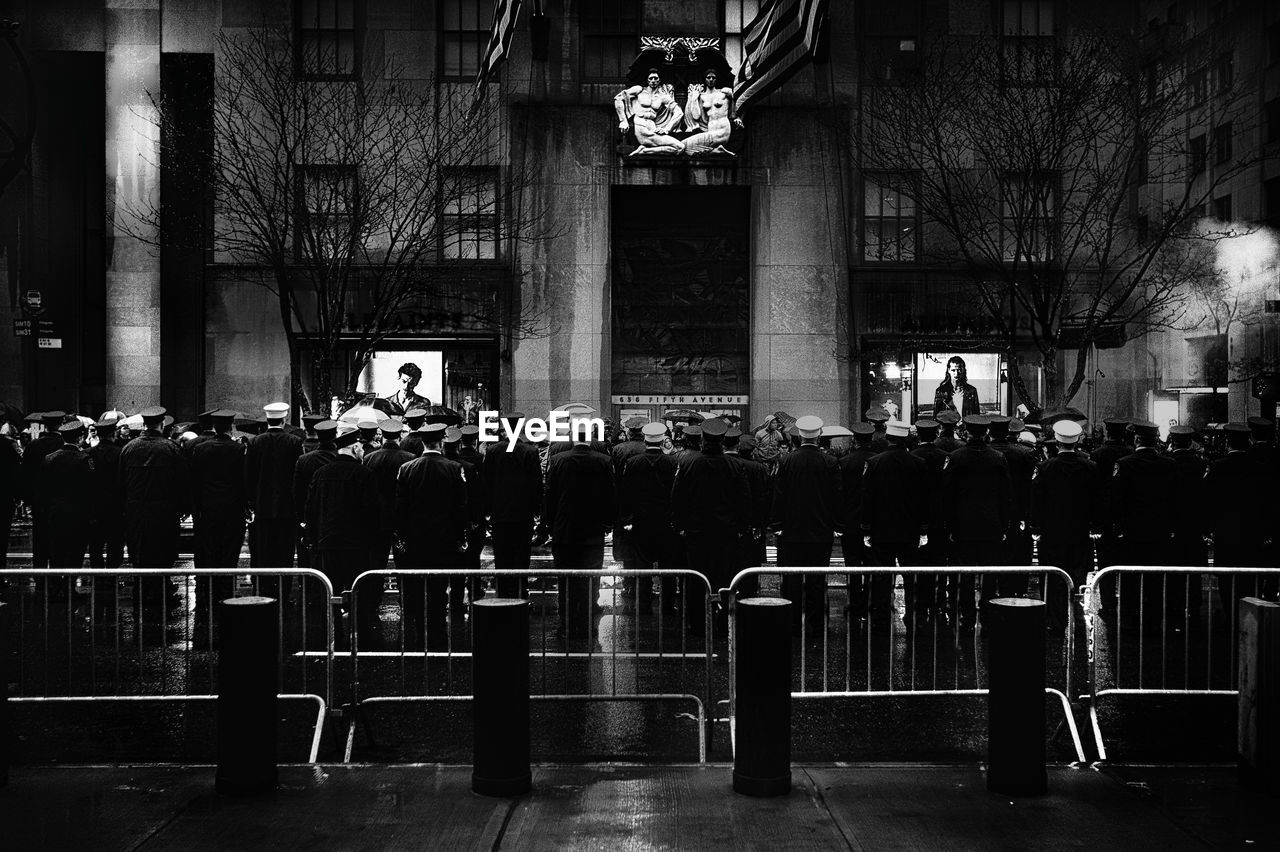 Crowd on street in city during funeral at night