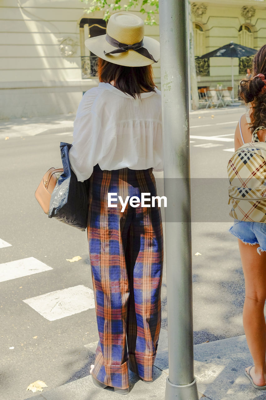 real people, rear view, women, lifestyles, city, adult, people, road, casual clothing, two people, leisure activity, street, day, standing, full length, transportation, walking, togetherness, clothing, architecture, outdoors, hairstyle, waiting
