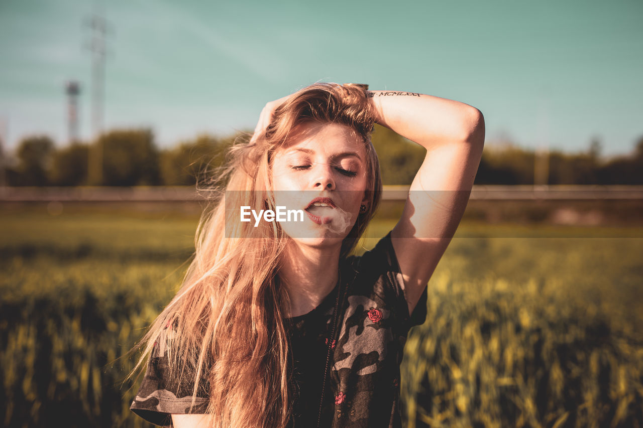 Beautiful Young Woman Exhaling Smoke On Field Against Sky