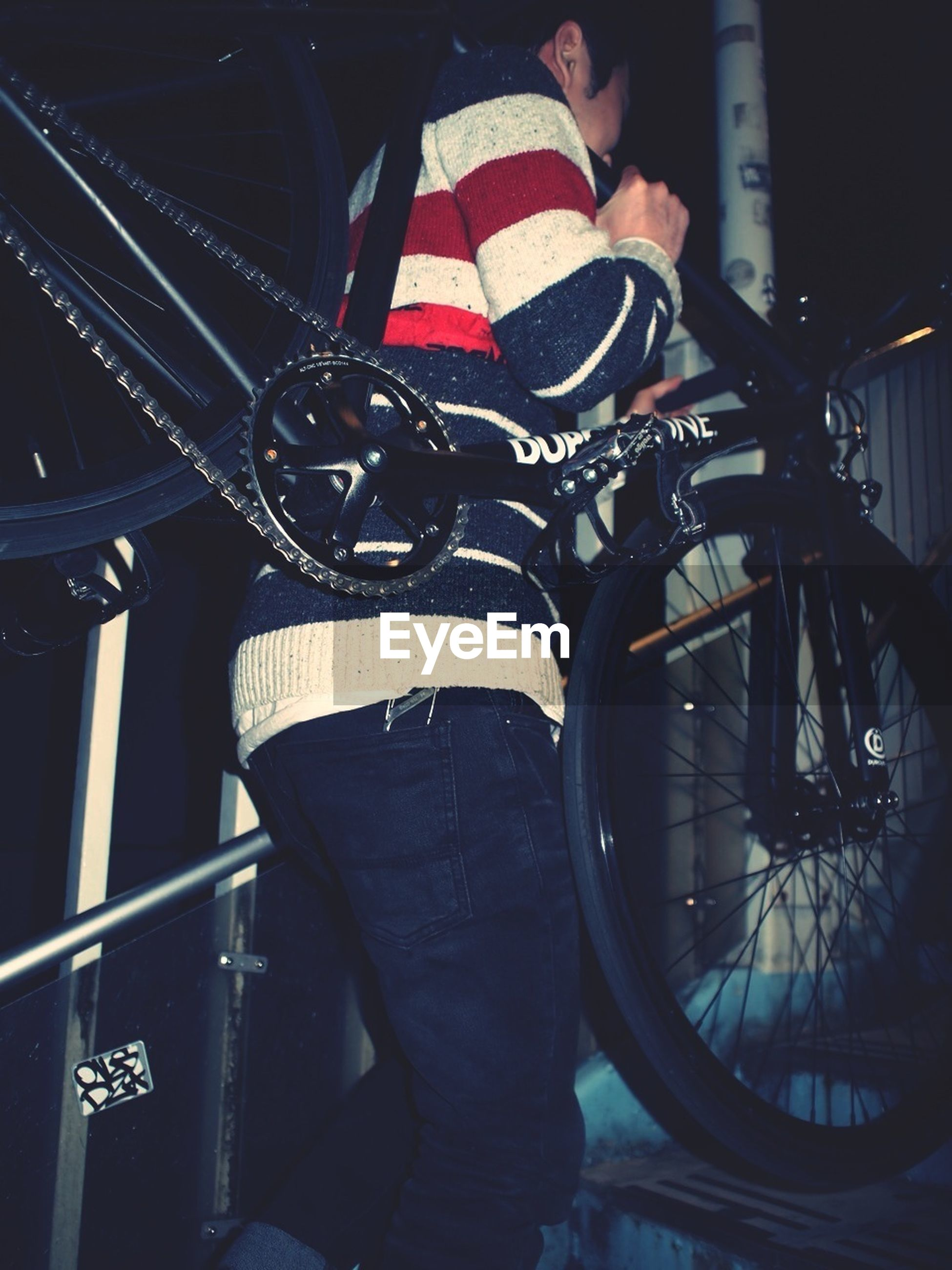 men, lifestyles, land vehicle, mode of transport, leisure activity, transportation, bicycle, casual clothing, low section, holding, indoors, standing, person, night, rear view, sitting