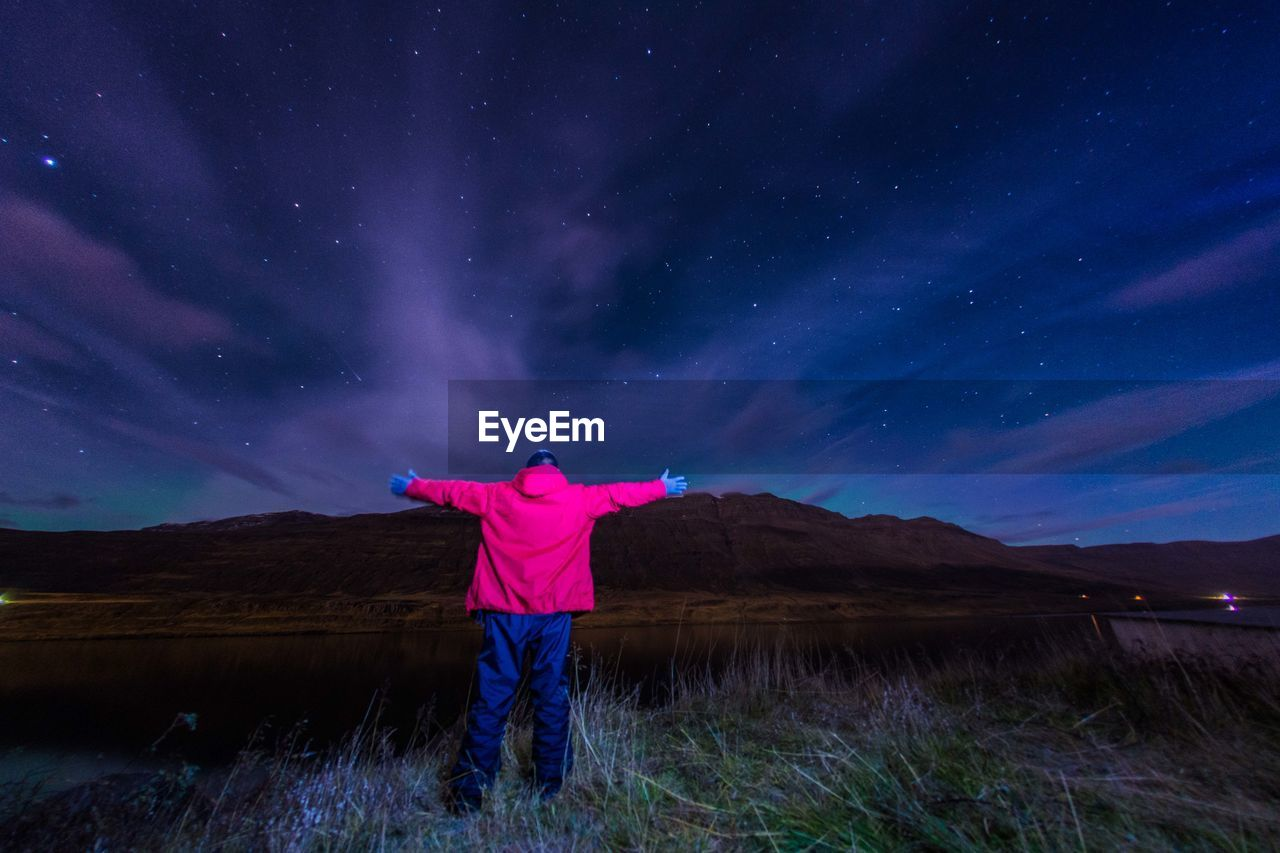 Rear View Of Man Standing On Field Against Sky At Night