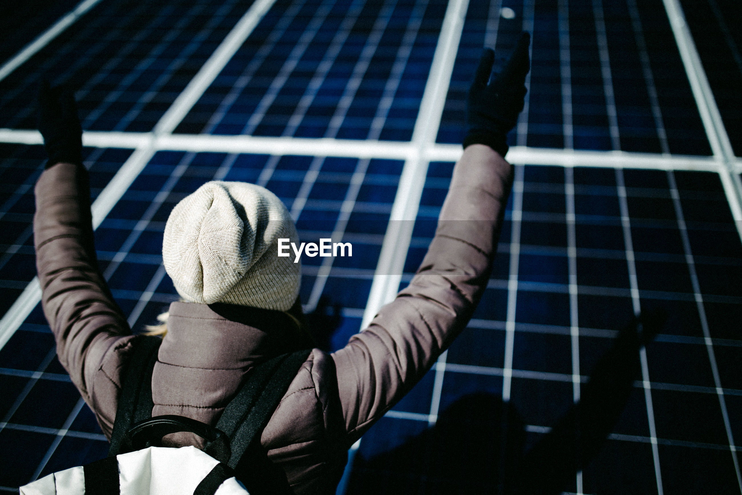 High angle view of woman in warm clothing by solar panel