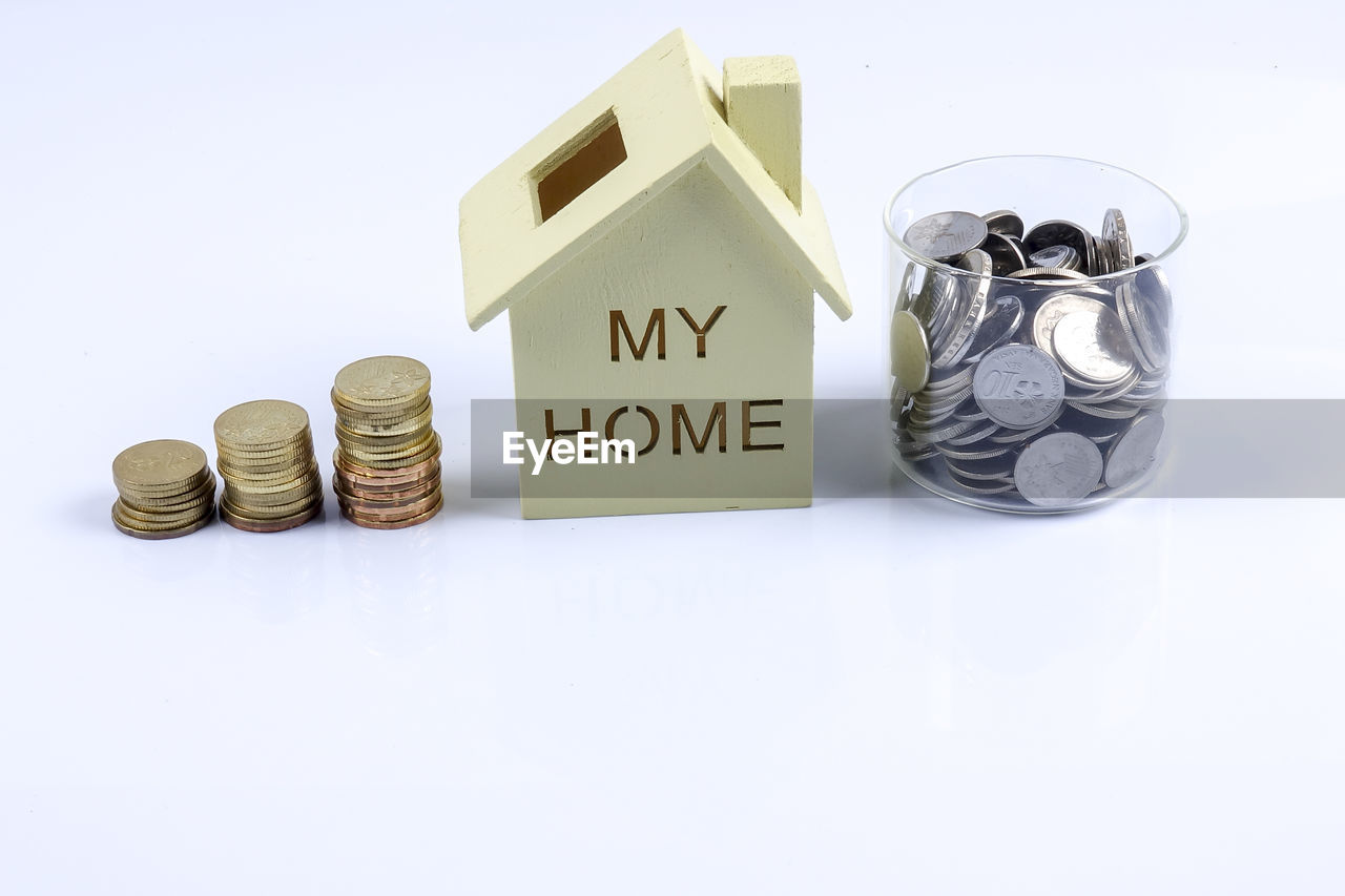 High angle view of home model with stacked coins against blue background