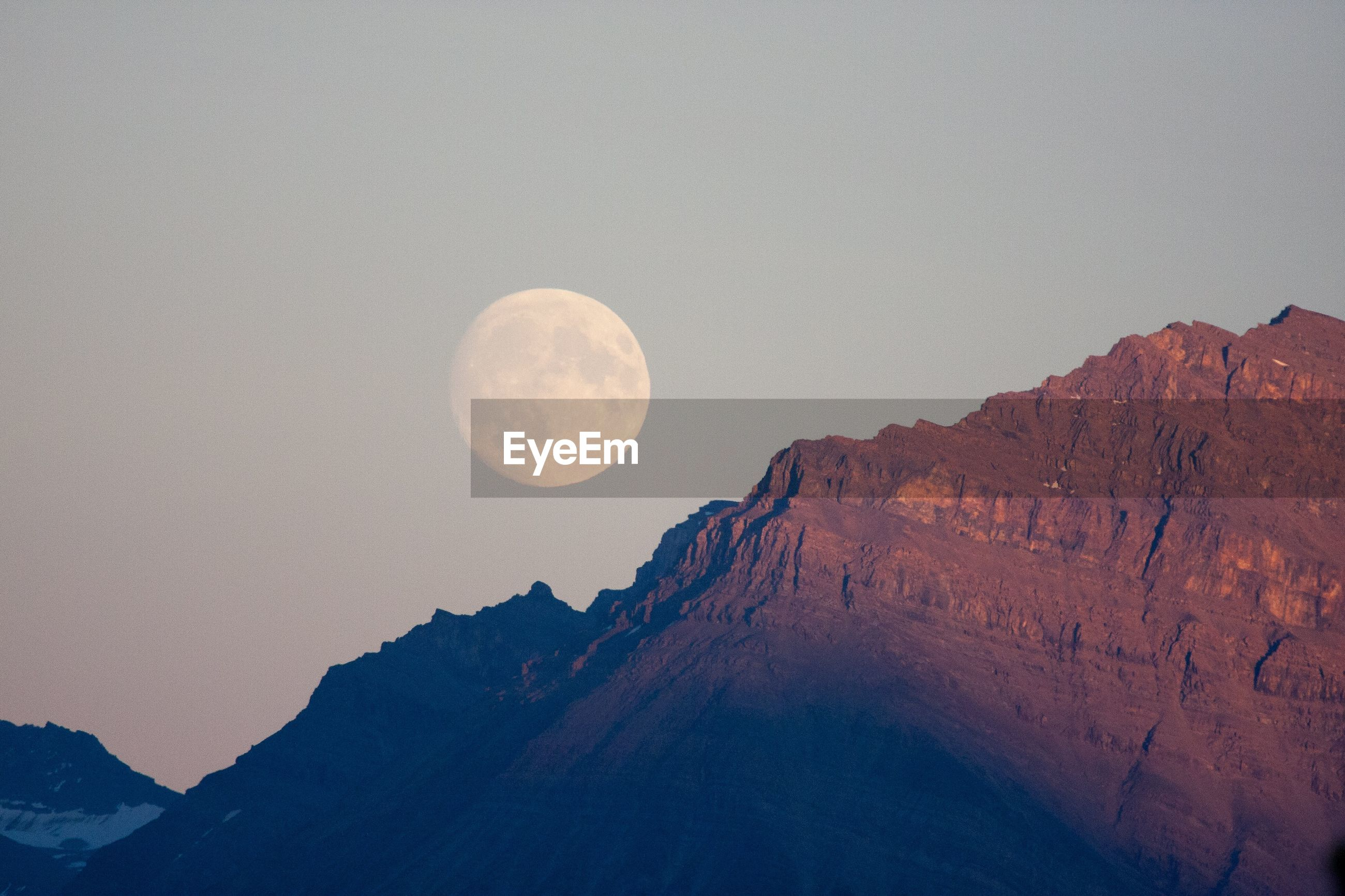 LOW ANGLE VIEW OF MOON AGAINST MOUNTAIN RANGE
