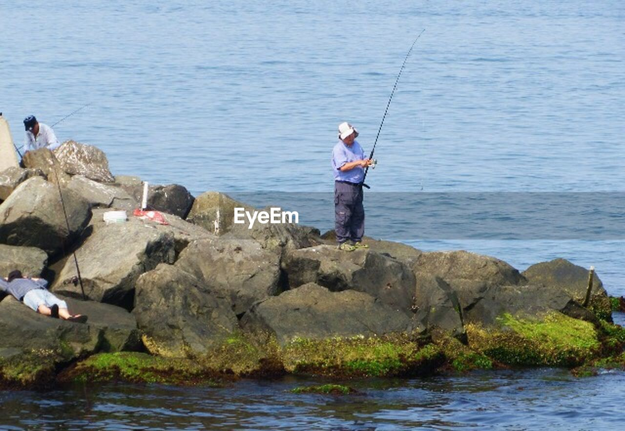 full length, sea, water, rock - object, standing, fishing, holding, day, outdoors, nature, one person, real people, men, fishing pole, adult, vacations, only men, people, adults only, one man only
