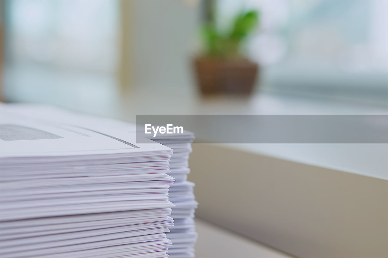 stack, table, indoors, focus on foreground, still life, paper, no people, large group of objects, close-up, white color, selective focus, office, business, publication, document, book, office supply, paperwork, balance, order
