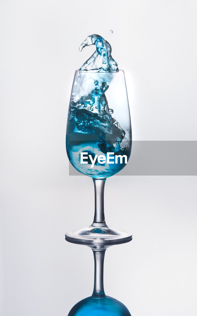 studio shot, white background, indoors, blue, no people, transparent, close-up, motion, glass, copy space, glass - material, water, cut out, nature, splashing, drop, gray background, drink, wineglass, purity, turquoise colored, high-speed photography