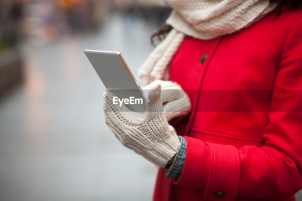 wireless technology, technology, communication, one person, women, warm clothing, connection, real people, scarf, leisure activity, midsection, jacket, winter, close-up, lifestyles, touch screen, outdoors, day, human body part, human hand, adult, people