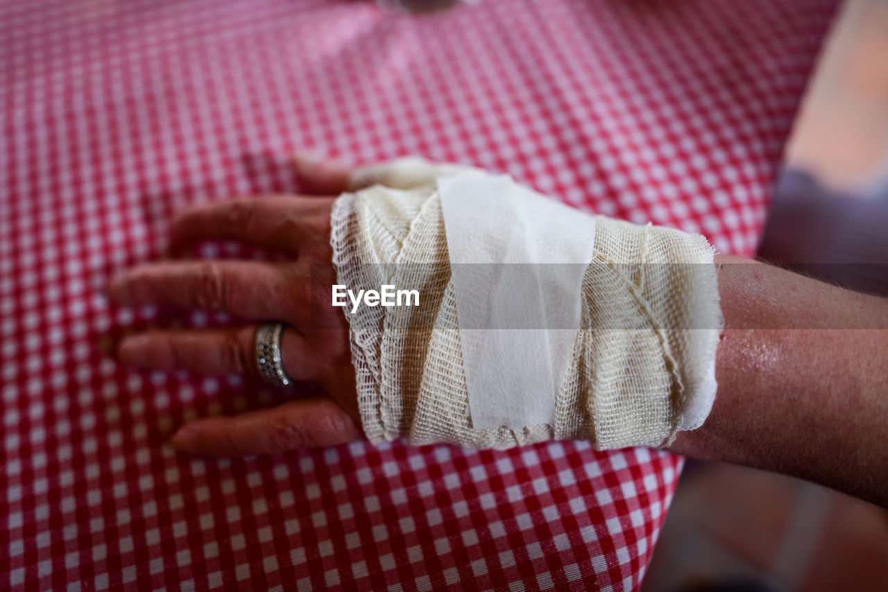 Close-up of woman hand with bandage on table