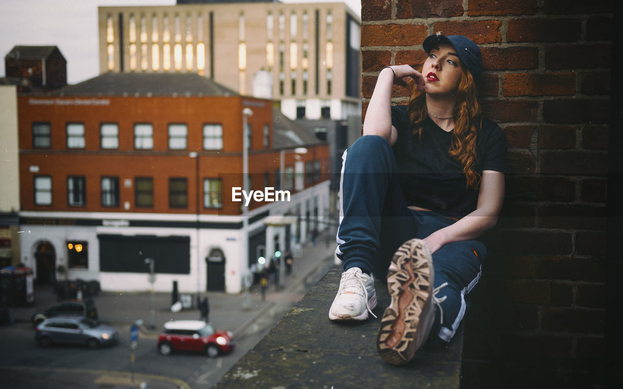 one person, real people, architecture, building exterior, built structure, lifestyles, young women, full length, leisure activity, young adult, sitting, city, casual clothing, day, street, women, front view, focus on foreground, outdoors, teenager, hairstyle, contemplation, depression - sadness