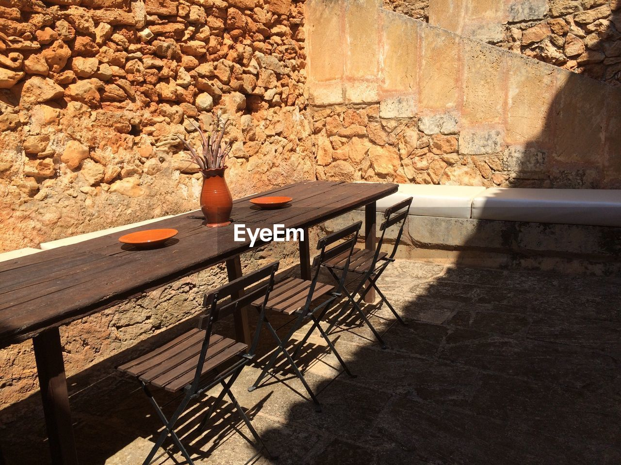 table, seat, no people, nature, chair, day, wood - material, stone wall, sunlight, architecture, shadow, wall, solid, wall - building feature, bench, built structure, indoors, absence, still life