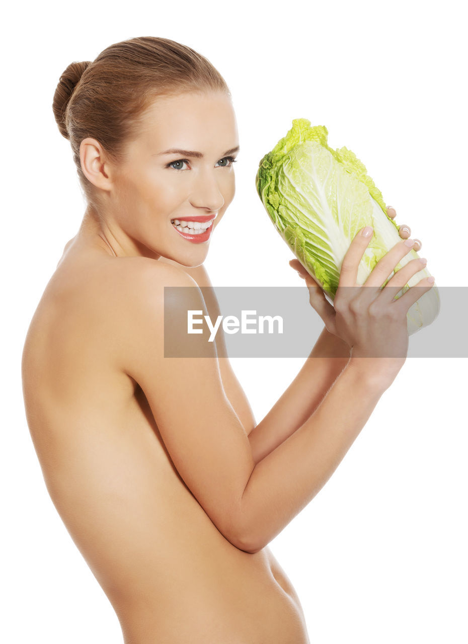 Portrait of smiling young woman holding lettuce against white background