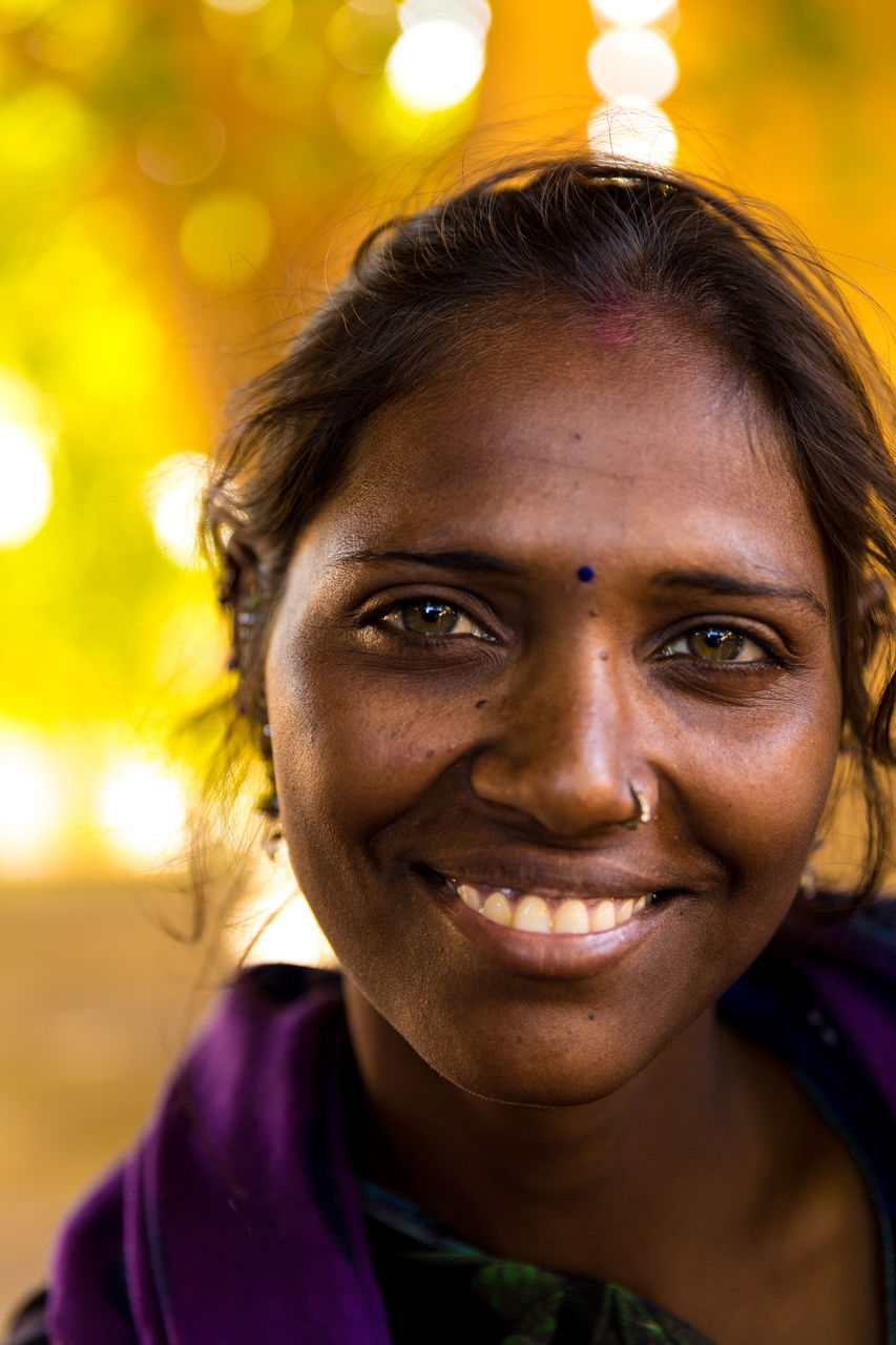 Portrait Of Smiling Woman Against Illuminated Lights