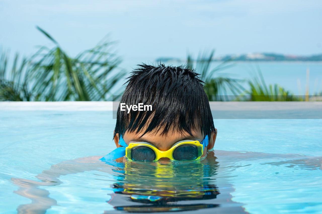 Portrait Of Boy Swimming In Pool Against Sky