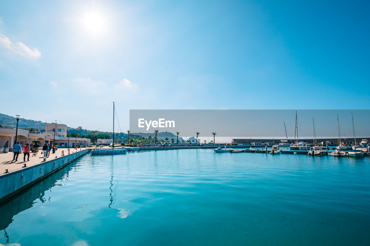 water, sky, transportation, nautical vessel, mode of transportation, nature, sea, waterfront, incidental people, day, reflection, cloud - sky, blue, harbor, sunlight, built structure, architecture, moored, scenics - nature, outdoors, sailboat, yacht, marina, swimming pool, luxury, bay
