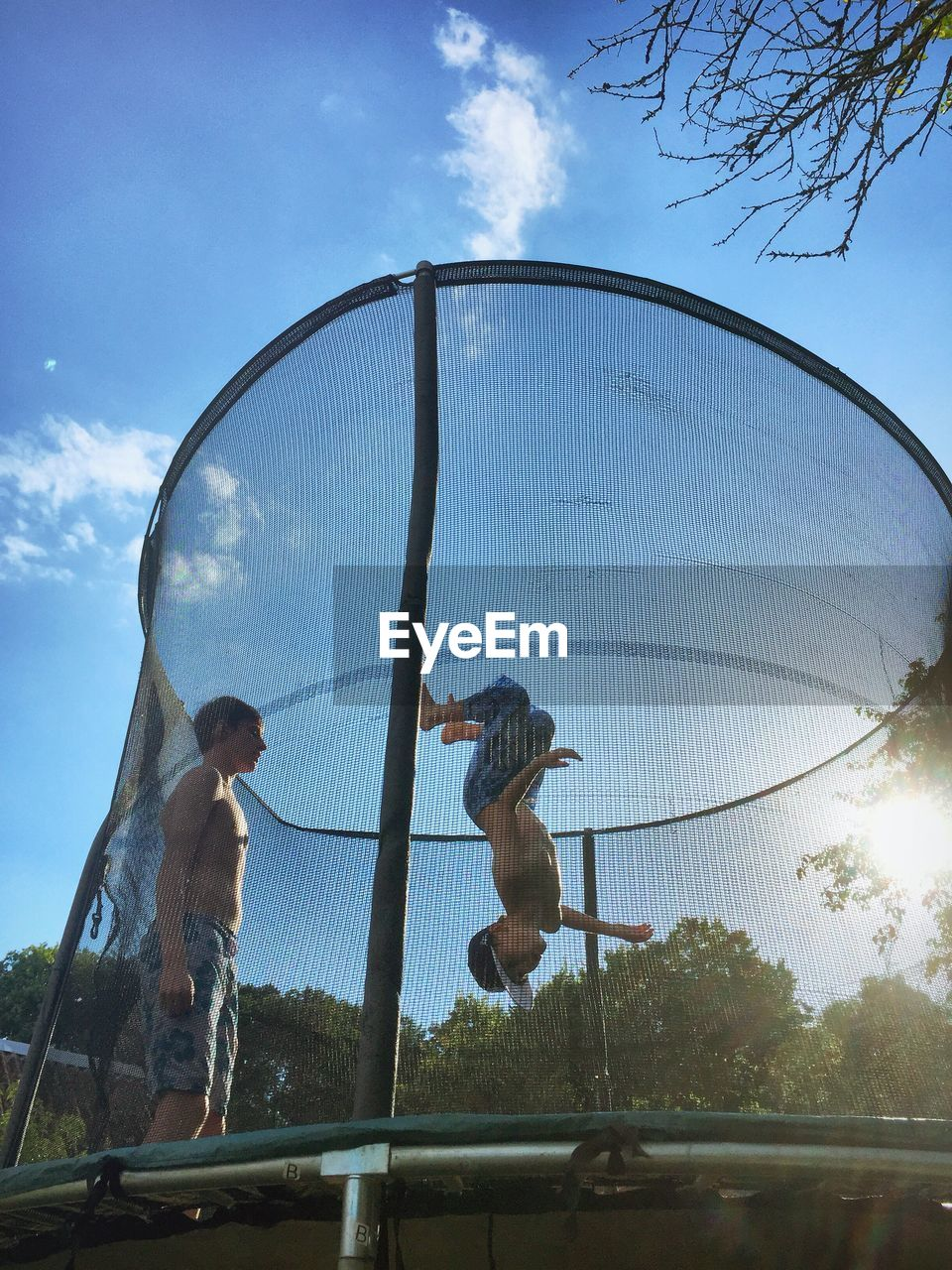 Shirtless boy looking at brother jumping in trampoline