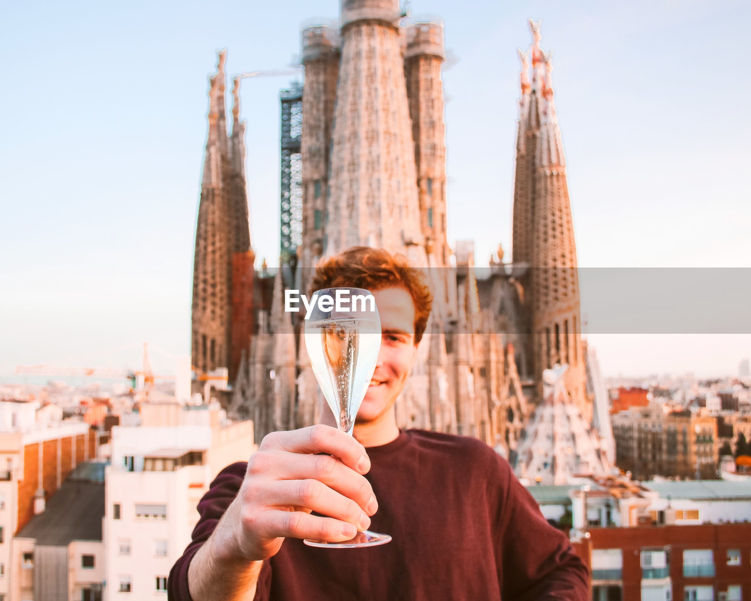 Man holding up a glass of champagne in front of sagrada familia