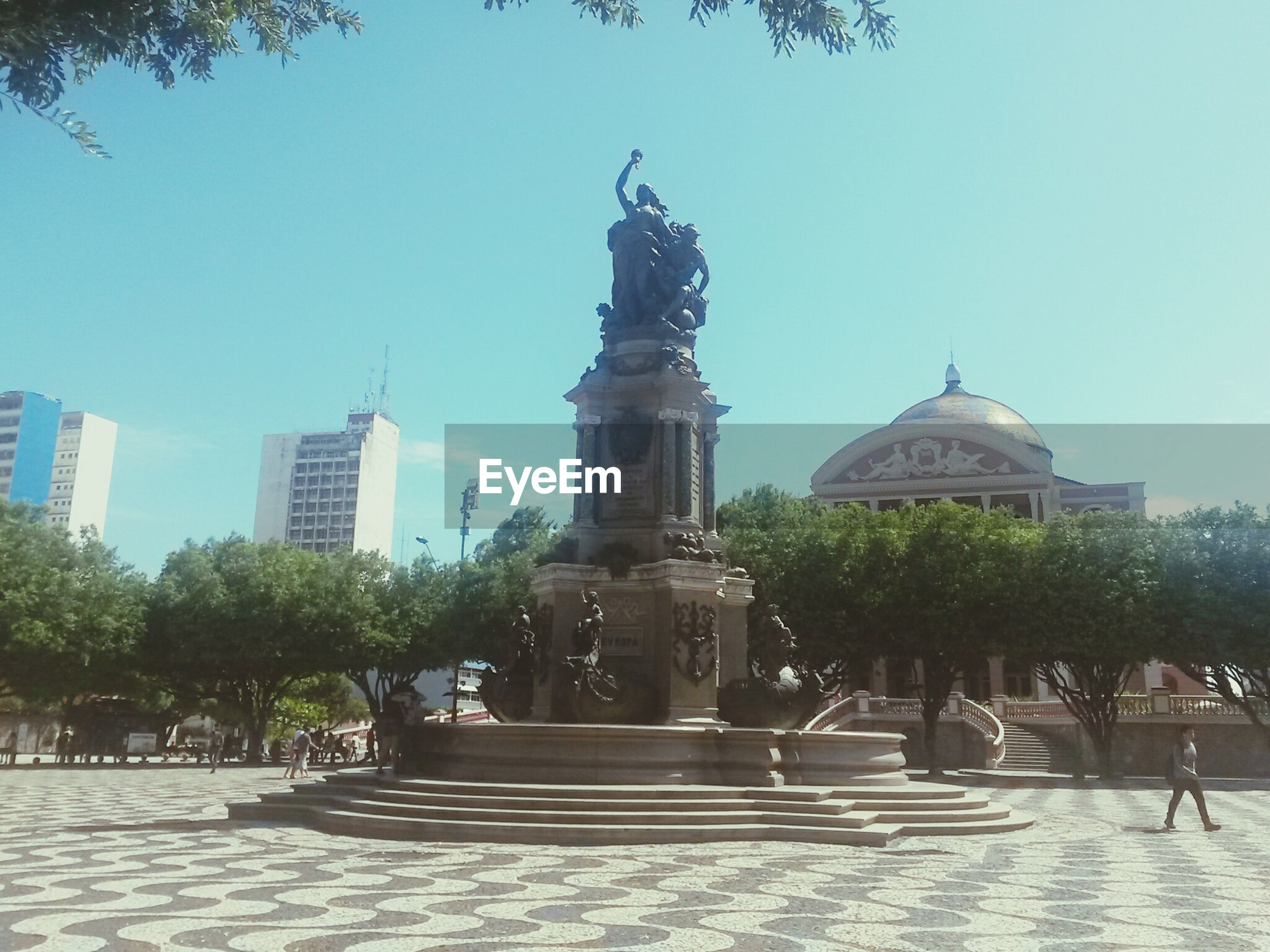 statue, sculpture, human representation, art and craft, clear sky, architecture, tree, art, built structure, building exterior, famous place, creativity, travel destinations, fountain, tourism, travel, incidental people, monument