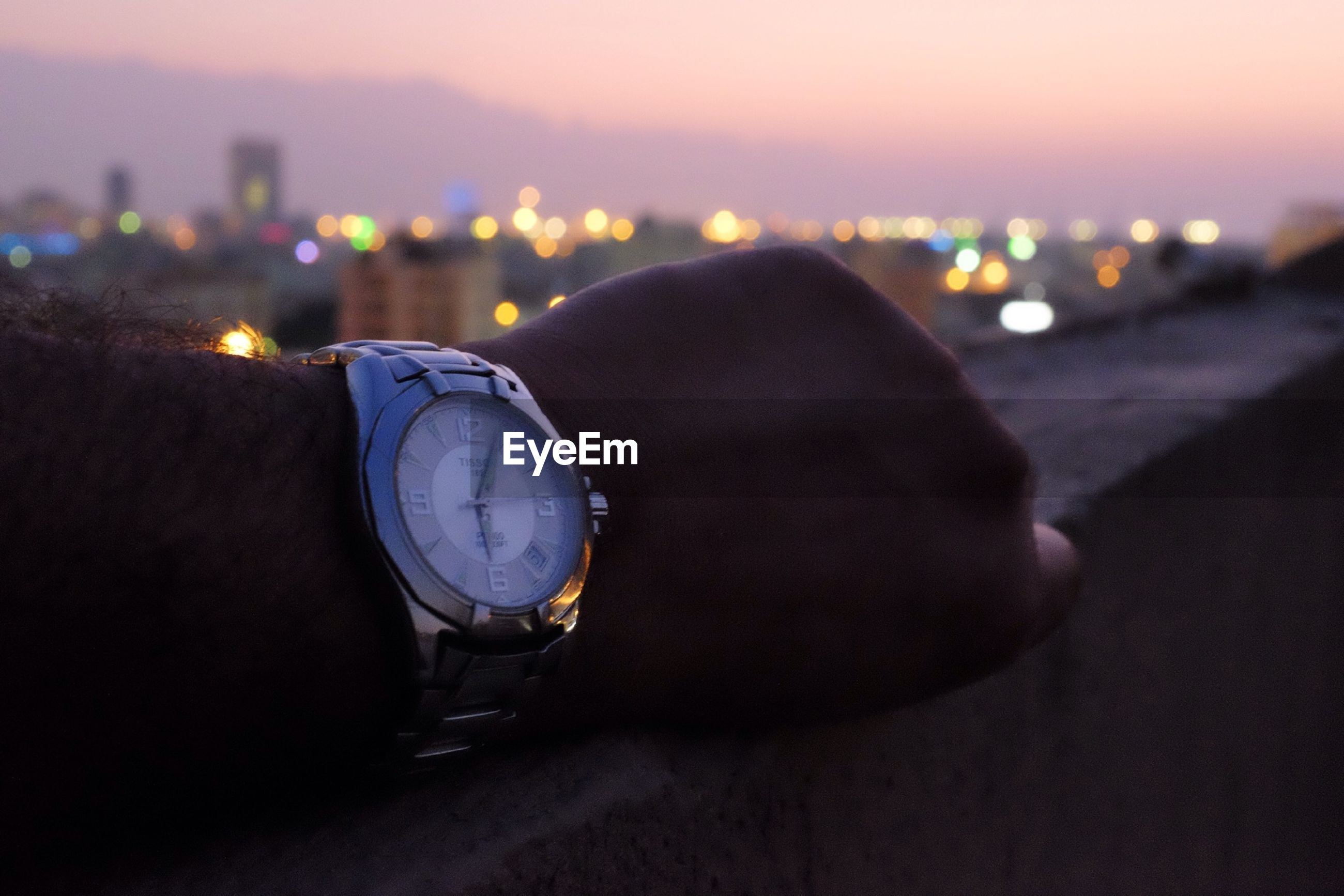 Cropped image of person showing wristwatch at dusk