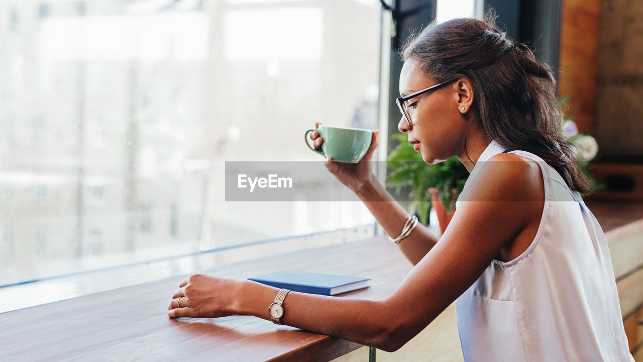real people, one person, lifestyles, focus on foreground, women, cup, drink, mug, adult, coffee cup, young women, holding, coffee - drink, indoors, young adult, casual clothing, females, refreshment, coffee, hairstyle, beautiful woman, contemplation, drinking