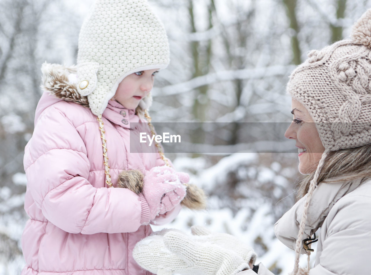 Mother And Daughter Playing With Snowball During Winter