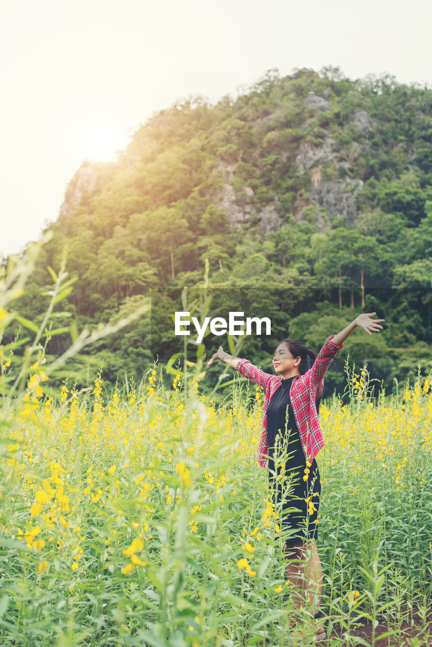 Woman with arms outstretched standing on field against mountain
