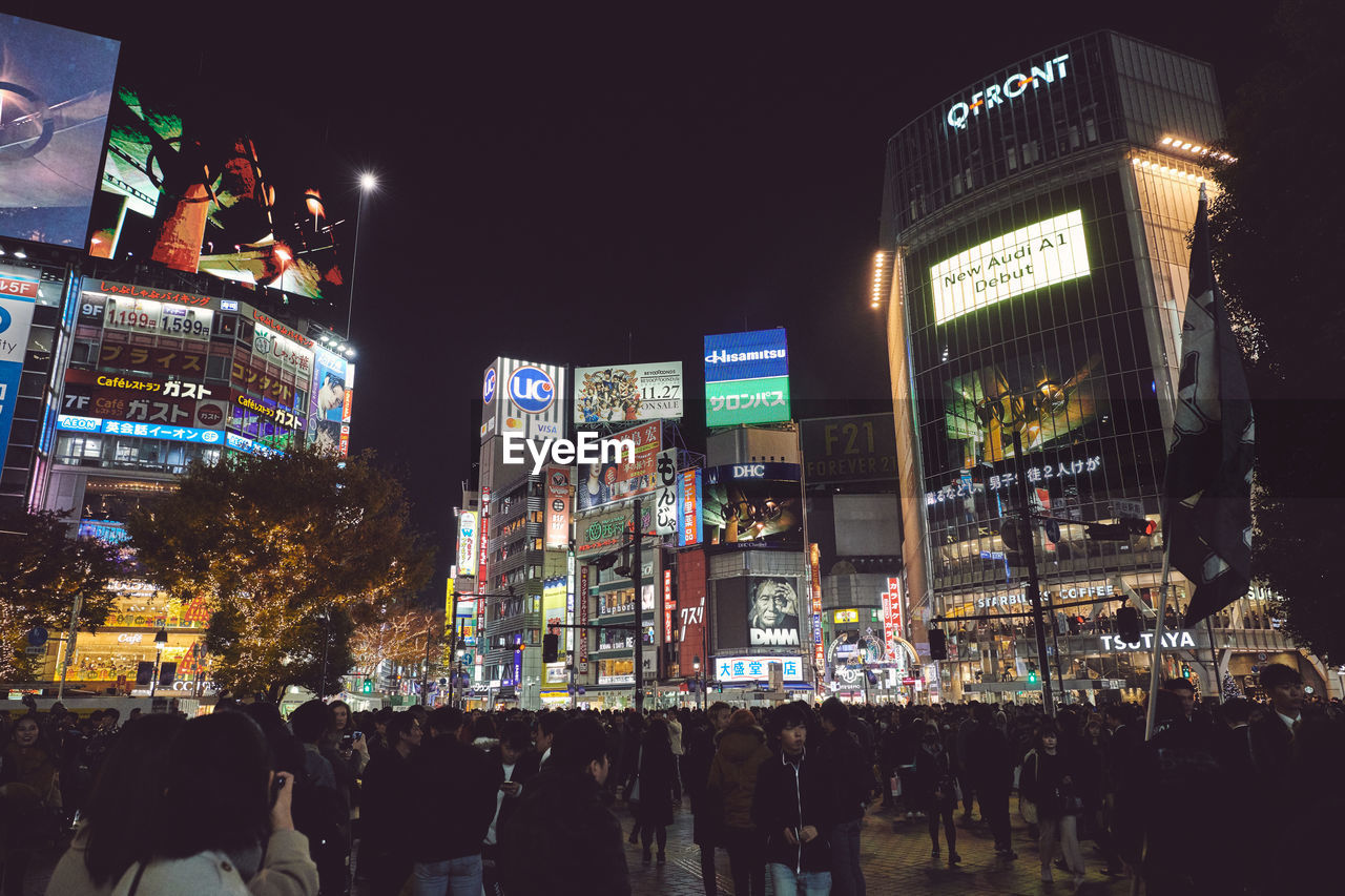 illuminated, night, city, building exterior, architecture, group of people, built structure, large group of people, real people, crowd, text, advertisement, women, communication, street, city life, men, billboard, building, nightlife