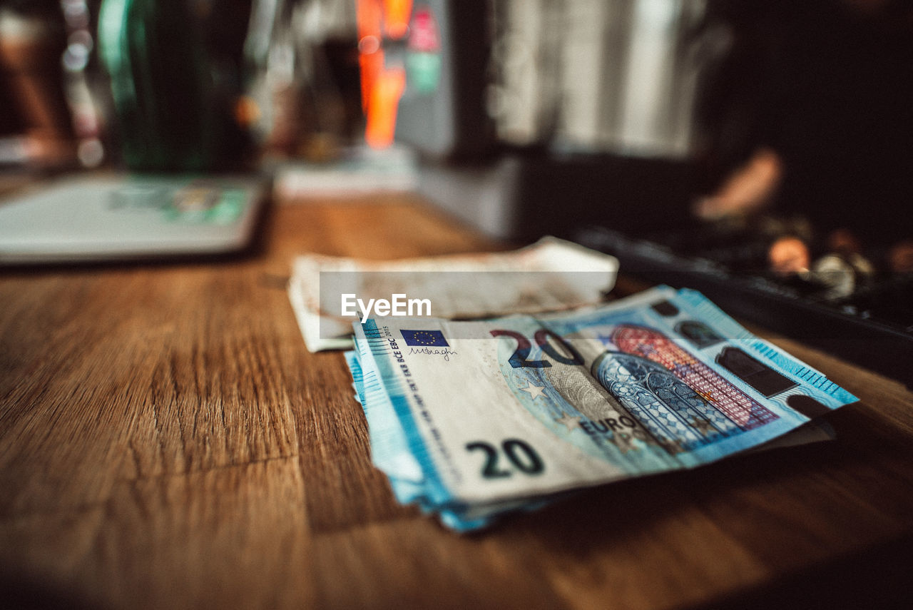 High Angle View Of Paper Currencies On Wooden Table