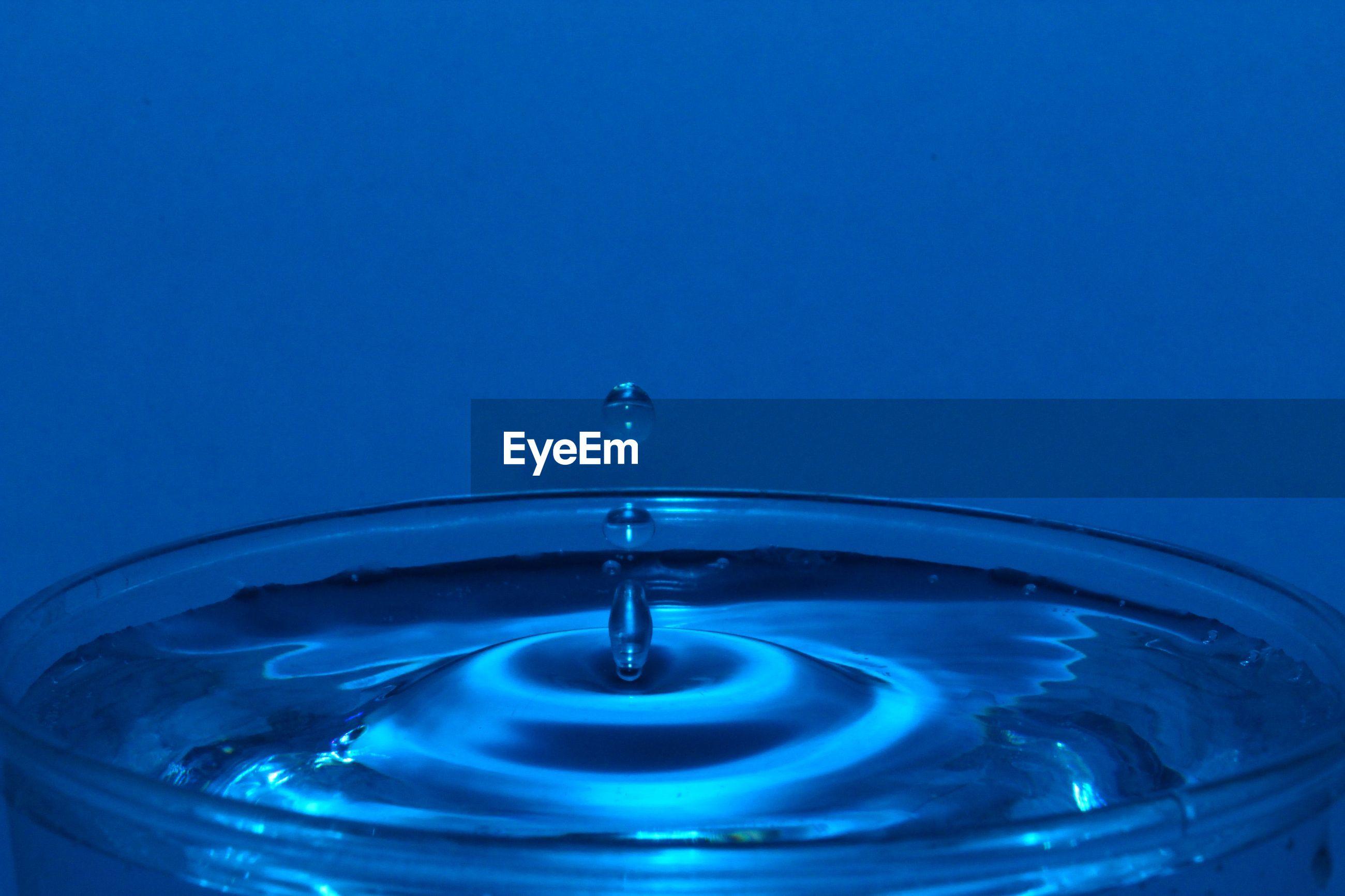 CLOSE-UP OF WATER DROP ON BLUE SURFACE