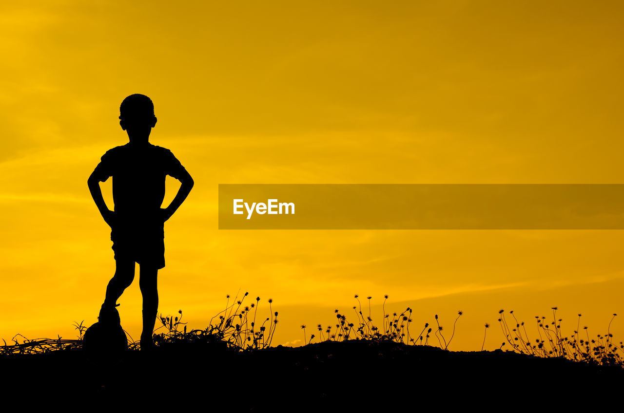 Silhouette Boy Playing With Ball During Sunset