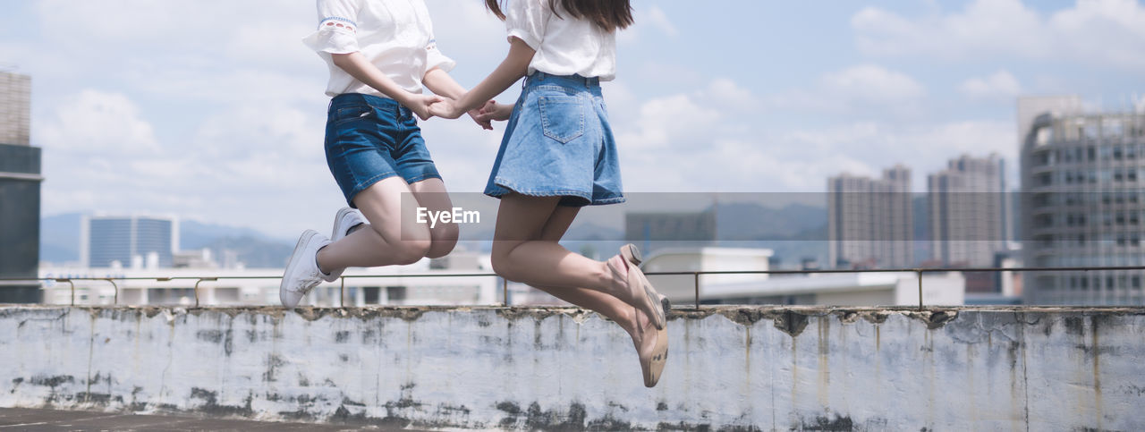 Low section of women jumping in city against sky