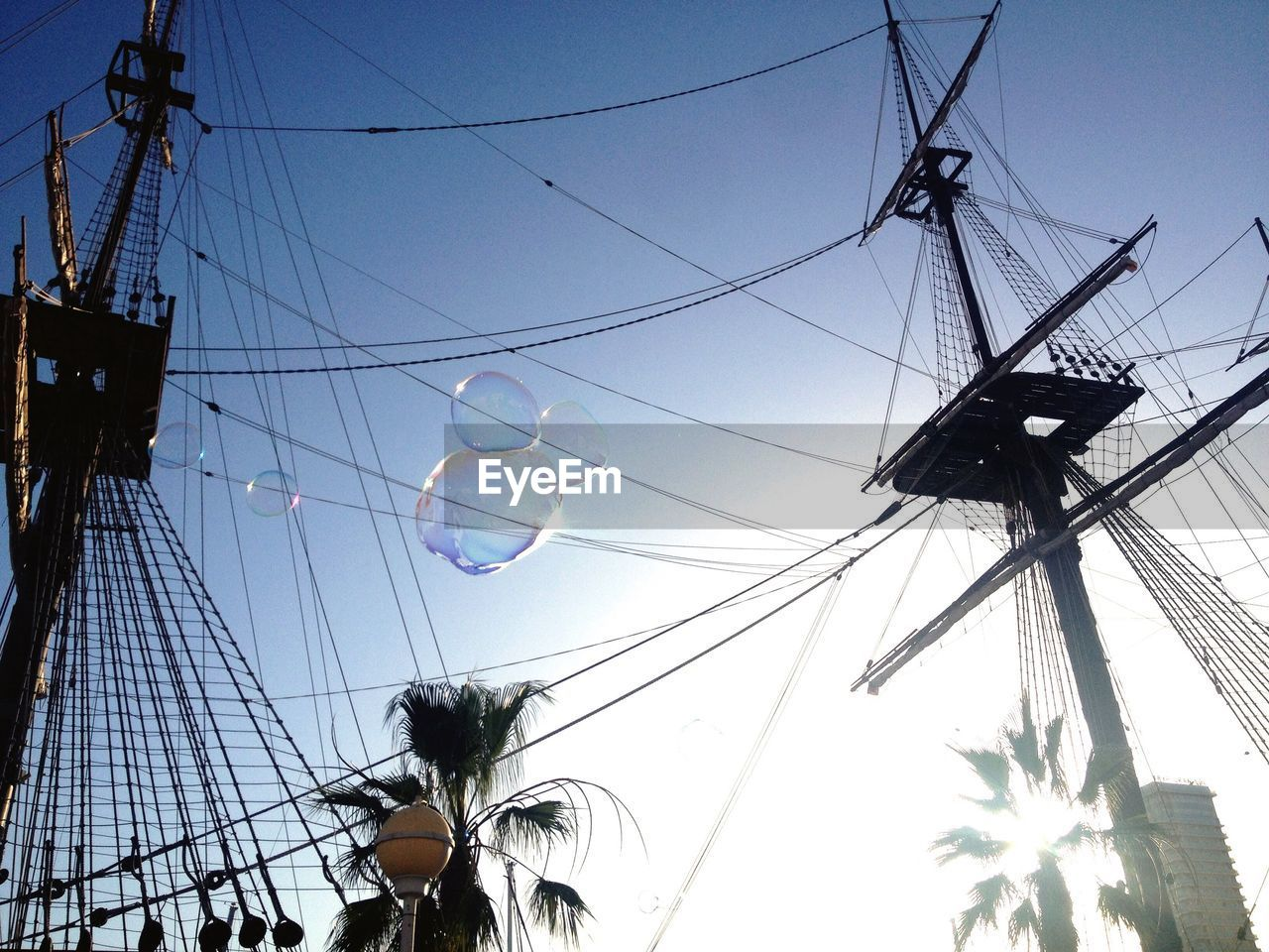 low angle view, sky, cable, nature, day, no people, electricity, pole, architecture, rope, outdoors, fuel and power generation, complexity, built structure, mast, connection, power line, clear sky, amusement park ride, tree, sailboat, power supply