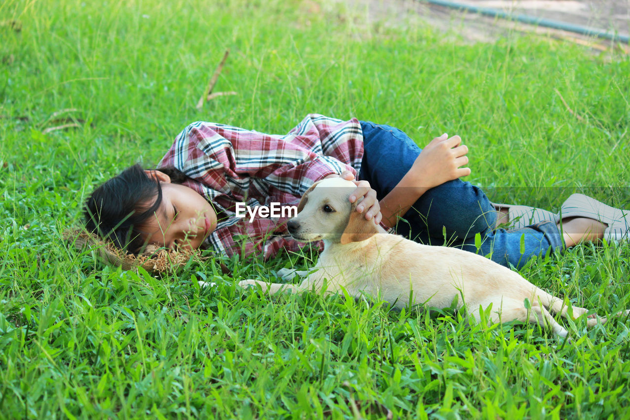 Girl Lying By Puppy On Grassy Field