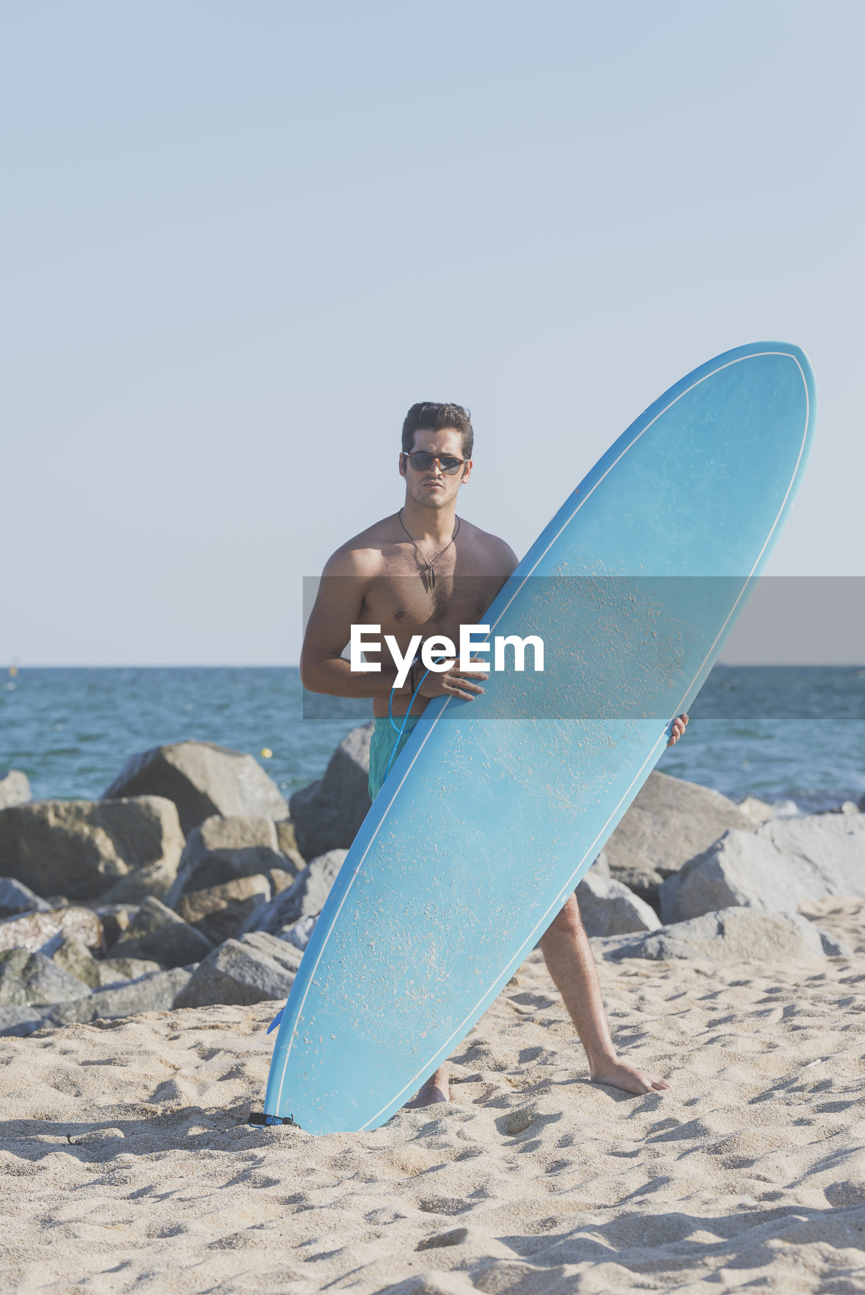 Full length of shirtless man with surfboard standing on shore at beach