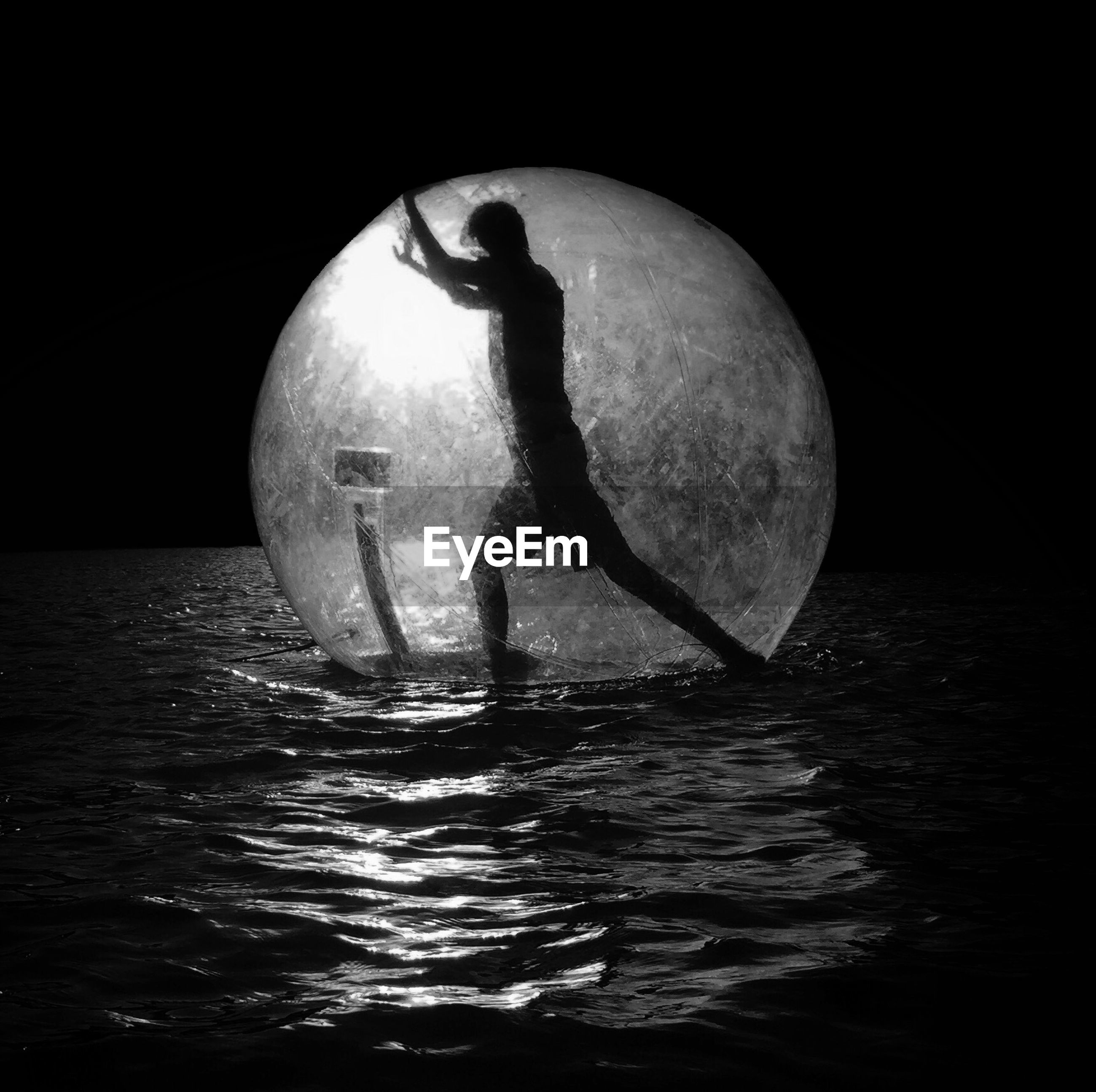 Side view of silhouette man in zorb ball on lake